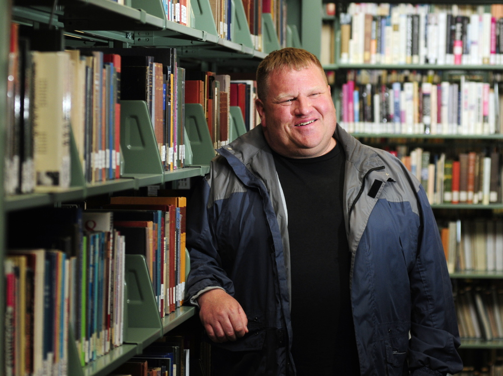 Commencement speaker and graduate Andrew Breault, 53, of South China, poses in the Katz Library last week at the University of Maine at Augusta.