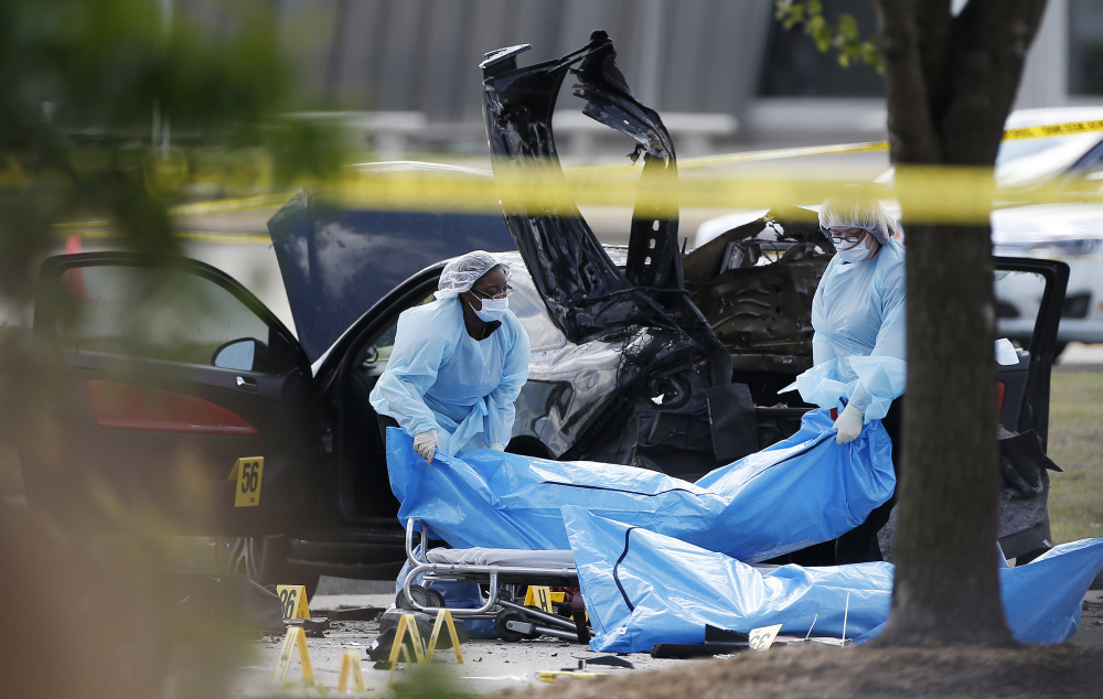 Personnel remove the bodies of two gunmen Monday, in Garland, Texas.