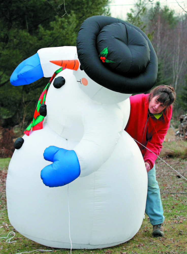 Tish Carr adjusts her inflatable snowman outside her home off Route 135 in Belgrade in this 2011 file photo.