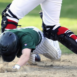 Winthrop High School's Adam Hachey dives between the legs of Hall-Dale High School catcher Sam Moulton to arrive safely at home during a Mountain Valley Conference game Monday in Farmingdale.