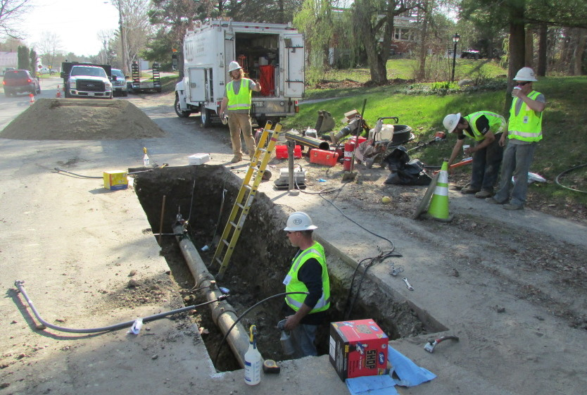 Employees from ETTI, a utilities construction company from Lisbon Falls, replace an electrofusion tee on a Summit Natural Gas line on Cool Street in Waterville Monday afternoon.