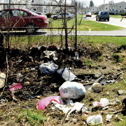 Will Henderson, a resident of the housing project off the Armory Road in Waterville, speaks on Monday about the accumulation of both bags of and loose garbage that lies in a culvert at the intersection of Wilson and Mystic streets. Some residents say the buildings and open space in the area are configured so that a wind tunnel effect results, blowing trash toward areas where barriers prevent it from being blown further along.