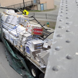 State Trooper Shawn Porter examines a tractor-trailer that struck the trestle on Water Street in Augusta Tuesday morning.