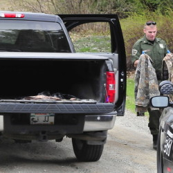 Game warden David Ross, left, and Winslow Detective Ron McGowen look over turkey hunting gear, including back packs and two shotguns, from a truck in Winslow on Tuesday. A man was taken to MaineGeneral Medical Center in Augusta with injuries to the face following a hunting accident with his wife.