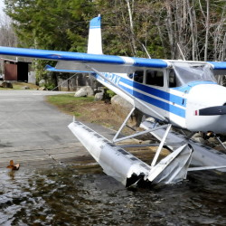 Plane owner Kenneth Comfort of Pittsfield looks over his heavily damaged 1965 Cessna 180 float plane at the Hartland town landing on Great Moose Lake on Tuesday.