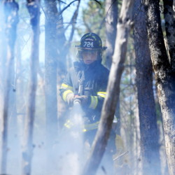 Jonathan Berringer, a firefighter with the Winslow fire department, battles a grass fire on Morrill Road in Winslow on Tuesday.
