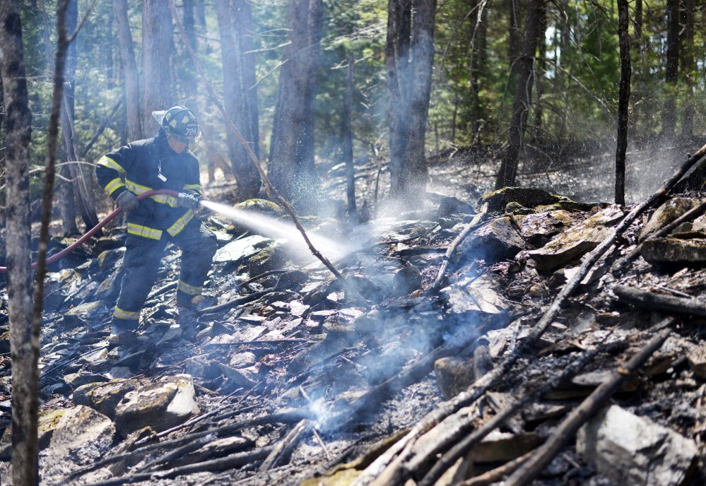 Jonathan Berringer, a firefighter with the Winslow fire department, fights a grass fire on Tuesday.