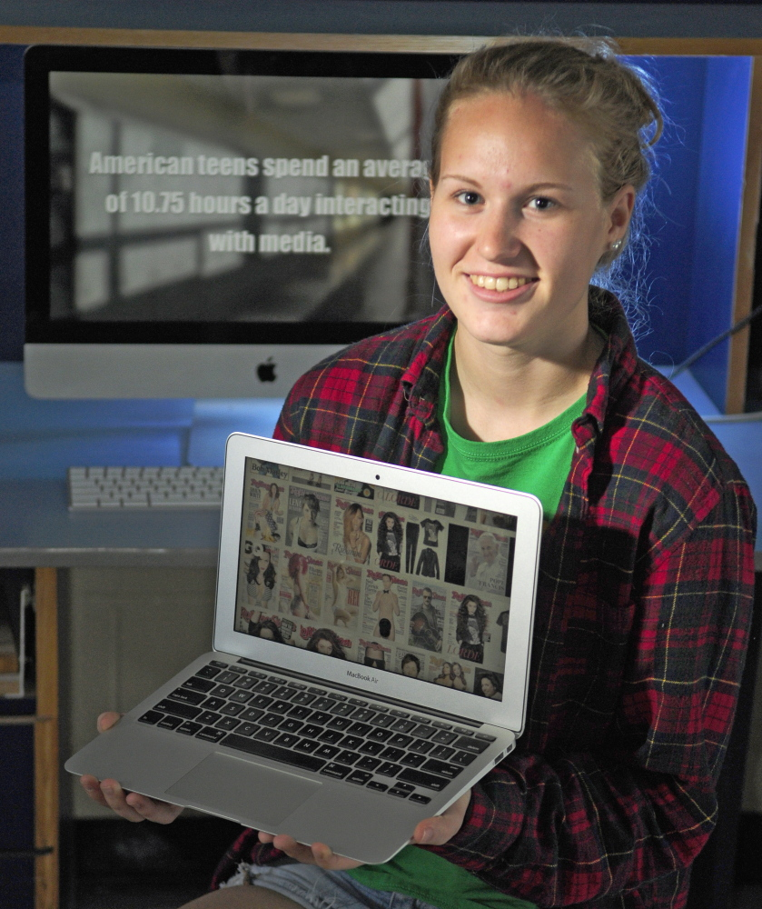"""Gardiner Area High School senior Emma Hickey poses Thursday in her broadcast journalism class with shots from her award-winning short film, """"Drop the Gender Mask,"""" on the screens."""