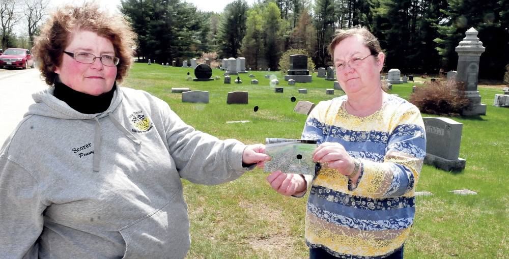 Penny Picard-Sampson, left, a member of the Unity Board of Selectmen and the Cemetery Committee, and committee member Lynn Warman hold a recent photograph of a Pond Cemetery grave covered with gravel and dust from nearby Kanokolus Road. The town converted the road from asphalt to gravel two years ago, and since then grave sites have been littered with rocks and dust. A group of citizens is asking the town to repave the road.