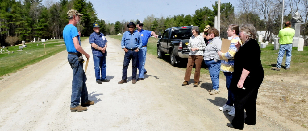 A group of Unity residents assemble on Thursday at the Pond Cemetery in an effort to convince the town to repave Kanokolus Road this summer. They argue that the road is the source of gravel and dust that litters the grave sites. There are times when debris is so thick that mowers will not use cutting equipment to maintain grass.
