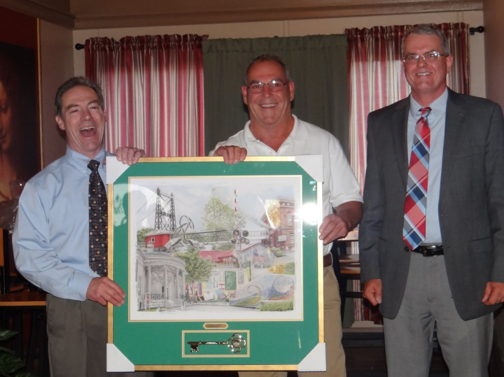 Waterville City Manager Mike Roy (right) and Downtown Main Street President Ronald Ducharme (left) present the Downtown Business of the Year Award to Silver Street Tavern owner Charlie Giguere Thursday at Amici Cucina in Waterville.