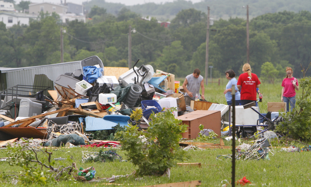 Neighbors and friends help clean up after Thursday night's tornado passed the area on Friday in New Fairview, Texas.