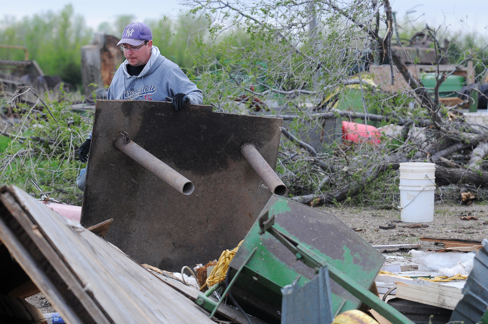 James Fink surveys the damage to family friend Mike Fechner's farm on Sunday near Delmont, S.D., after a tornado tore through the area damaging homes and businesses on Sunday morning.