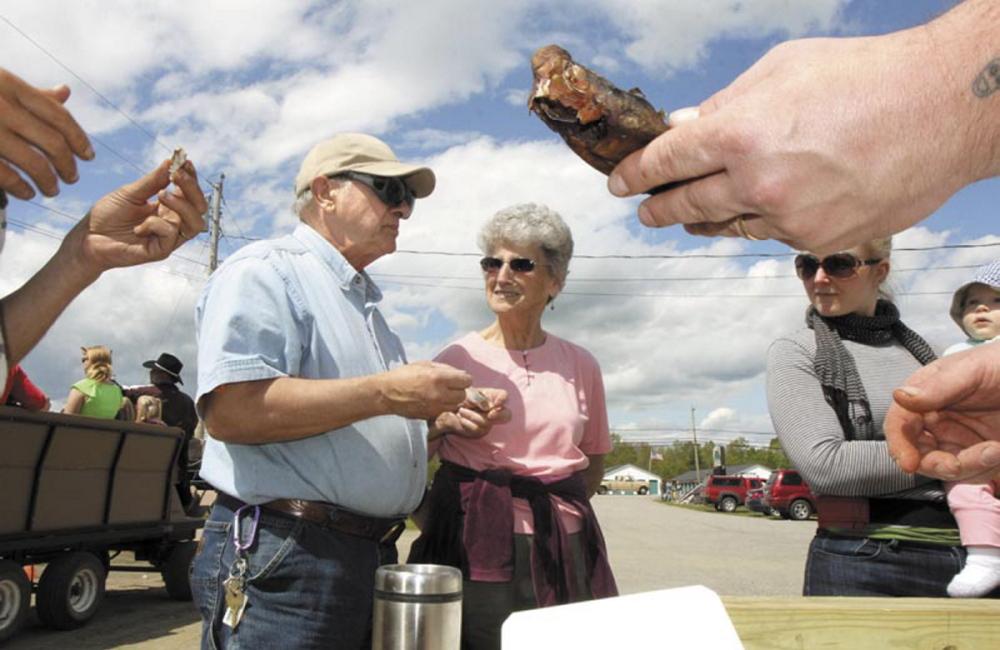 Erma Blakney, of Fairfield, center, looks over as her friend, Edward Fisher, tastes a smoked alewife during the 2013 Benton Alewife Festival. Smoked alewives are on the menu for Eating with the Alewives, a community dinner that kicks off the annual festival on Friday night.