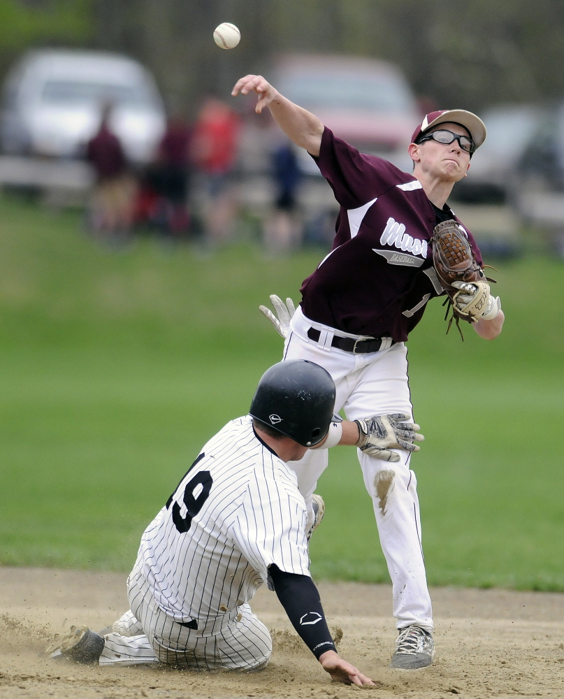 Monmouth Academy's Mat Foulke attempts to turn two after making the tag at second during a game against St. Dom's on Monday afternoon.
