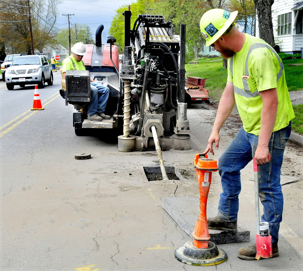 Subcontractors for Summit Natural Gas of Maine guide a drill under the surface of North Street in Waterville on Tuesday while work continues on the company's natural gas pipeline system in Waterville.