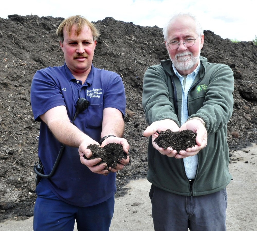 Al White, left, and Randy Gray hold handfuls of rich compost from organic material processed at the Regional Recycling Center in Skowhegan on Wednesday.