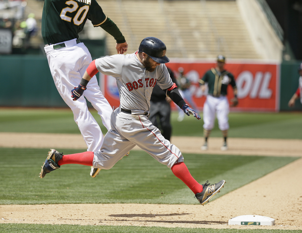 Boston Red Sox second baseman Dustin Pedroia runs safely to first base as Oakland Athletics first baseman Mark Canha leaps for the throw in the eighth inning Wednesday in Oakland, Calif. The Red Sox won 2-0.