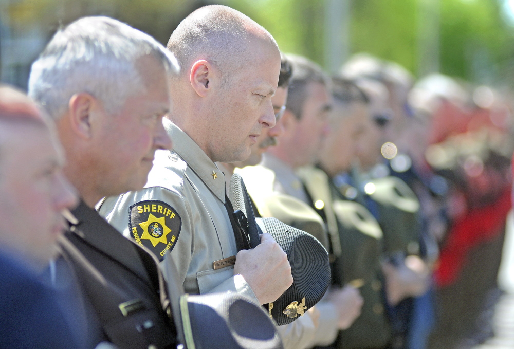 Law enforcement officers, including Penobscot County Chief Deputy William Sheehan, listen Thursday during the annual police memorial ceremony in Augusta.