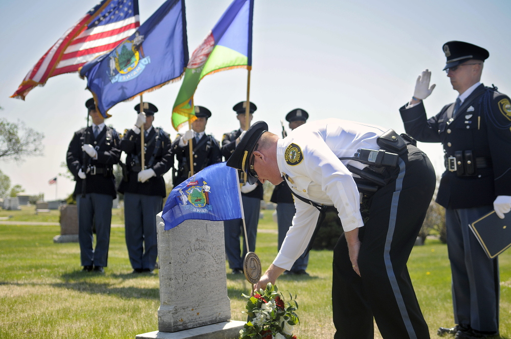 Augusta Police Deputy Chief Jared Mills places a wreath Thursday on the headstone of Augusta police officer Selden Jones, who was killed in the line of duty in 1930.