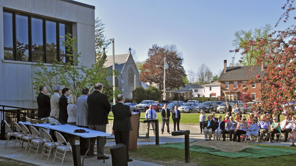 People sit on chairs listening to speeches on Thursday during a ceremonial groundbreaking for Lithgow Library expansion in Augusta. The part of the building at top left will be demolished, and the new expansion will be built onto the grass and parking lot seen in the background.