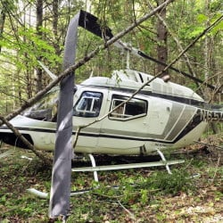 A helicopter sits in the woods after a crash landing on Friday May 30, 2014, in Whitefield.