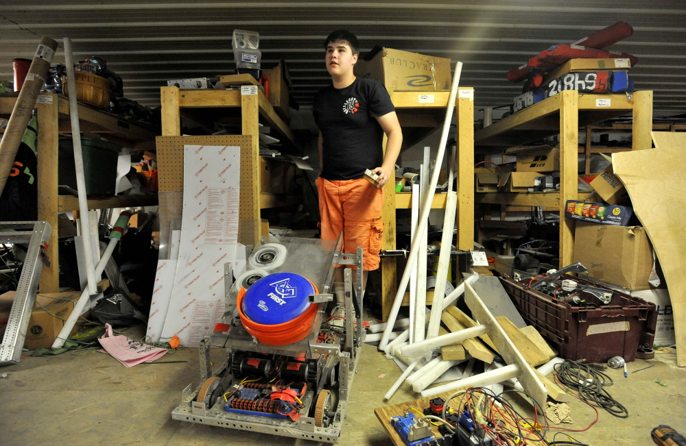 Delsin Klein, 14, emerges from shelves of parts as he works on the Messalonskee robotics team robot on Thursday at Wrabacon in Oakland.