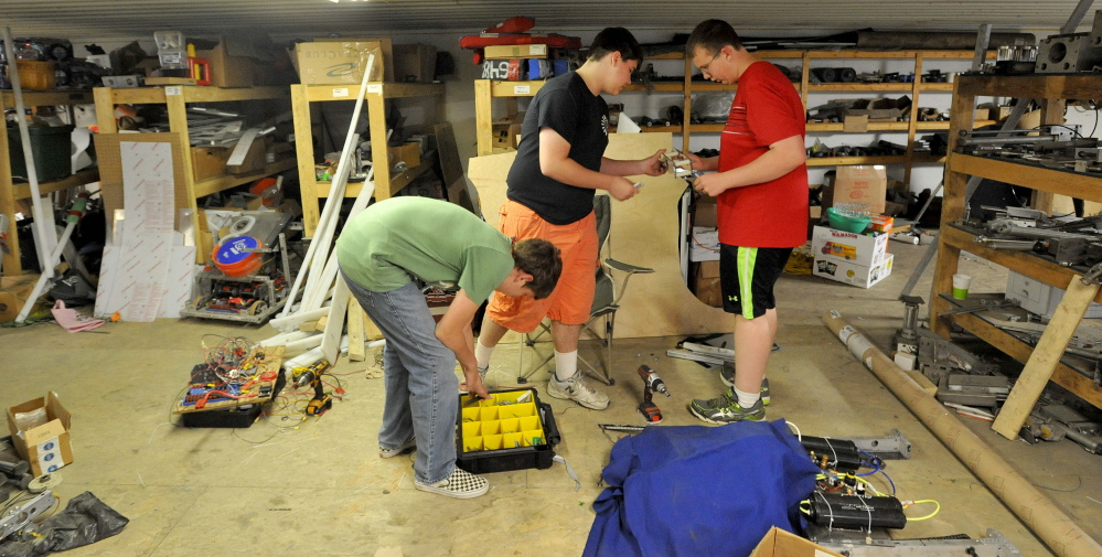 Delsin Klein, 14, center, fabricates parts for the Messalonskee robotics team robot on Thursday with teammates Geoffery Fotter, 15, left, and Ethan Pullen, 16, right, at Wrabacon in Oakland.