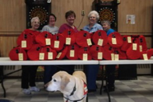 American Legion Auxiliary Unit 39 members from Madison donated their time to fill the 20 duffel bags for DHHS. From left are Betty Dow, Harriet Bryant, Robin Turek, Marie Wing and Merrilyn Vieira. Colonel, service dog to Turek, is in the front.