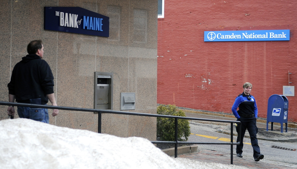 People walk out of The Bank of Maine branch, left, and Camden National Bank on Water Street in Gardiner in this March file photo. Camden National announced Friday that it plans to consolidate bank branches that are near each other, including these locations in Gardiner.