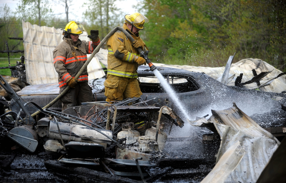 Kyle King with the Burnham fire department, right, and Ryan-Michael Havery with the Pittsfield fire department, mop up a garage fire on Webb Road in Pittsfield on Saturday. Firefighters were dispatched around 1:30 in the afternoon. The garage was a total loss.