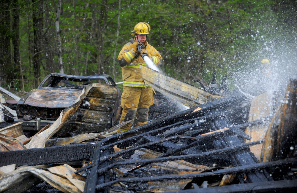 Kyle King with the Burnham fire department mops up a garage fire on Webb Road in Pittsfield on Saturday. Firefighters were dispatched around 1:30 in the afternoon. The garage was a total loss.(