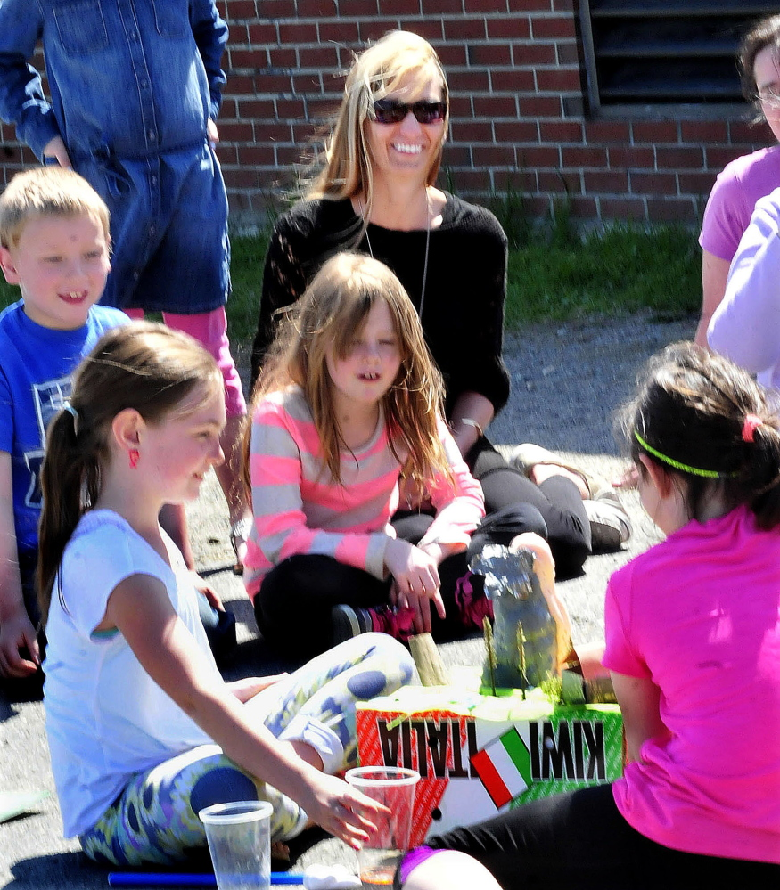 Athens Community School teacher Amy Bown watches on Thursday as students Sydney Sillanpaa, left, and Lily Cooley demonstrate a simulated volcano eruption.
