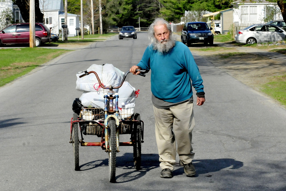 Neil Woodard wheels his bike loaded with a basket full of returnable cans and bottles he collected off Skowhegan streets and from residents on Sunday. Woodard has collected the items daily for years.