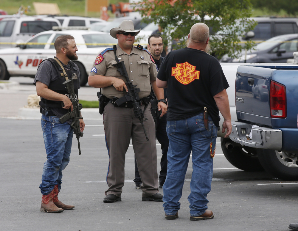 Law enforcement officers talk to a man near the parking lot of a Twin Peaks Restaurant Sunday in Waco, Texas, after a shooting involving rival biker gangs.