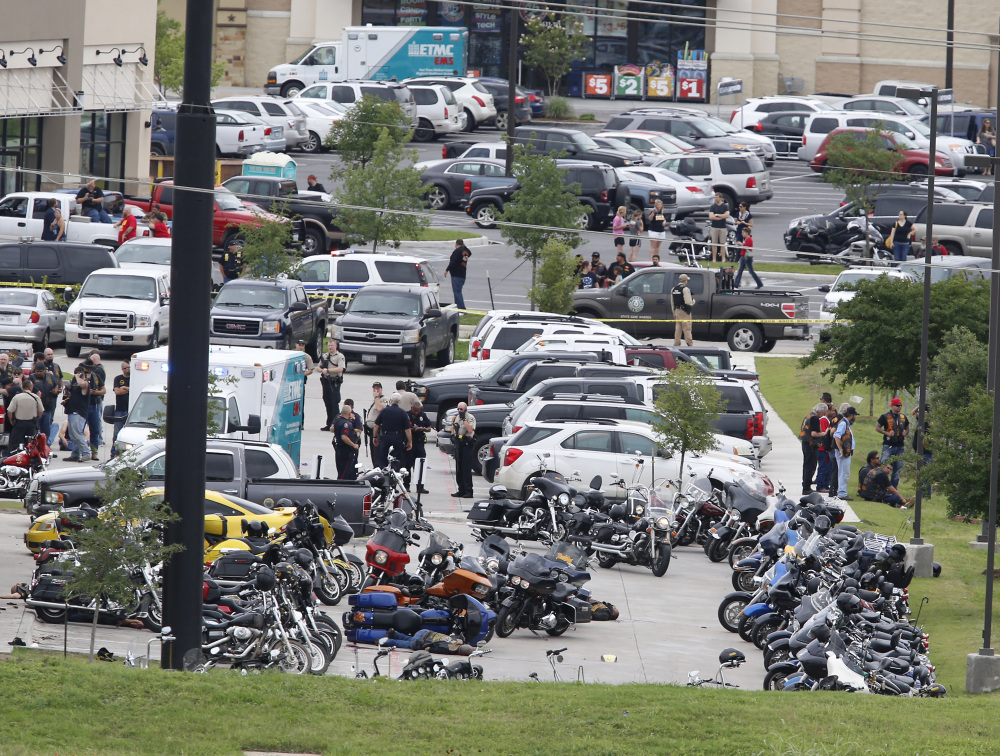 Law enforcement officers investigate a shooting in the parking lot of the Twin Peaks Restaurant Sunday in Waco, Texas.