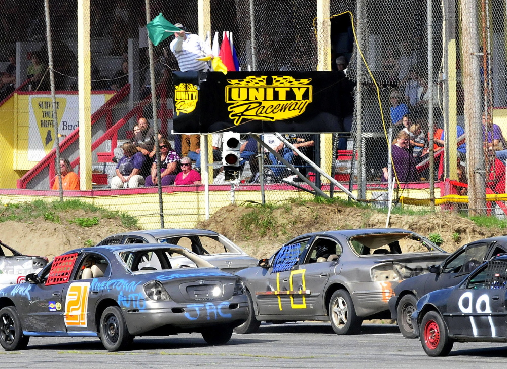 Unity Raceway flagger Jeff Overlock waves the green flag to restart the first Super Stock Enduro race during the season opener Sunday in Unity.