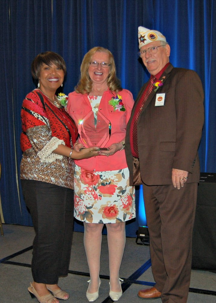 Lorna Hatch, center, chief of Voluntary Service, VA Maine Healthcare System in Augusta, recently was given national honors in a ceremony that awarded her the VA Voluntary Service Award for Excellence. The award is based on accomplishments in leadership, volunteer growth, program development, community involvement and staff development, all for the benefit of the Veterans she serves. At right is Sabrina Clark, director, Voluntary Service Office, VA Central Office, and at left is Bill Kilgore, AMVETS national VAVS representative and chairman, VA Voluntary Service National Advisory Committee. The VAVS Award for Excellence was presented April 23 at the 2015 VAVS National Advisory Committee meeting in Albuquerque, New Mexico.