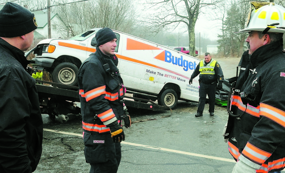 Gardiner police and firefighters remove a van that rolled over Dec. 31, 2011, and claimed the lives of two men and injured a third on ice-covered U.S. Route 201 in Gardiner.