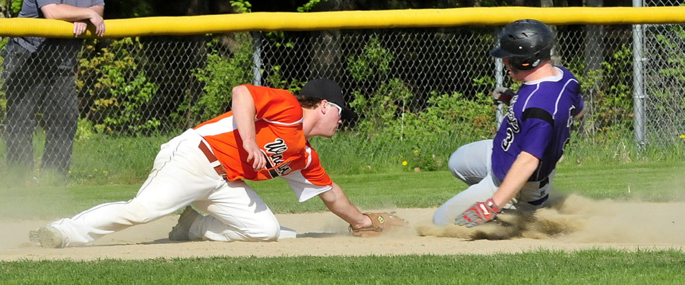 Winslow's Dylan Hapworth, left, tags out Waterville baserunner Dan Pooler during a game Monday in Winslow. The Black Raiders beat the Purple Panthers 5-0.