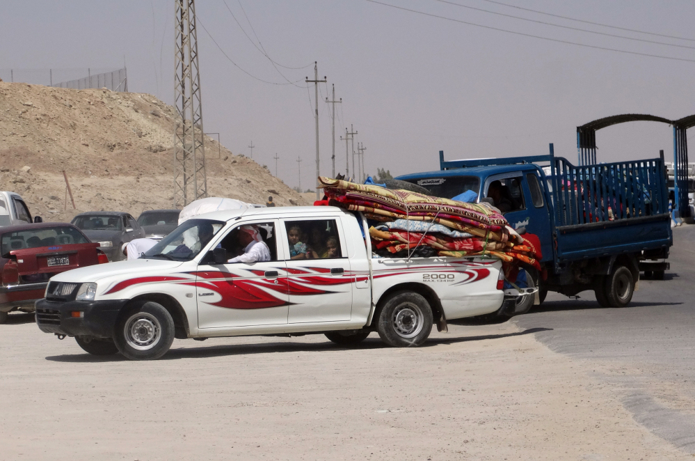 In this Monday, photo, civilians fleeing their hometown of Ramadi, Iraq, pull over their pickup truck at a police checkpoint as they drive through Habaniyah town, 80 kilometers (50 miles) west of Baghdad.