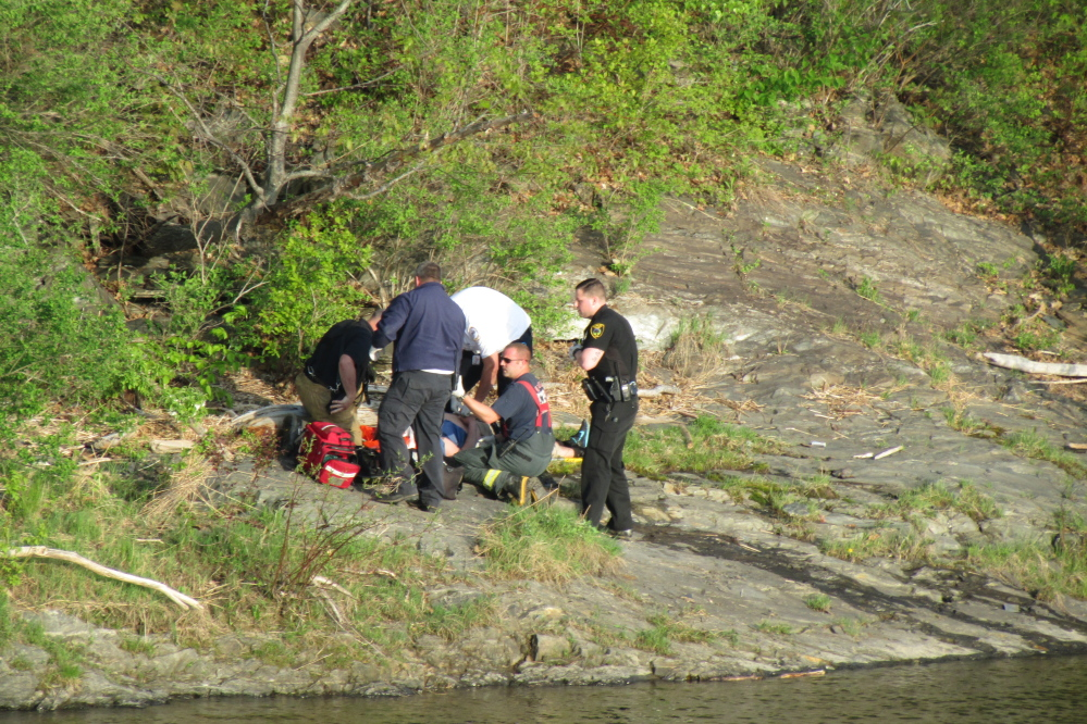 Emergency workers help a reportedly unresponsive man on the bank of the Kennebec River in Winslow on Tuesday evening.