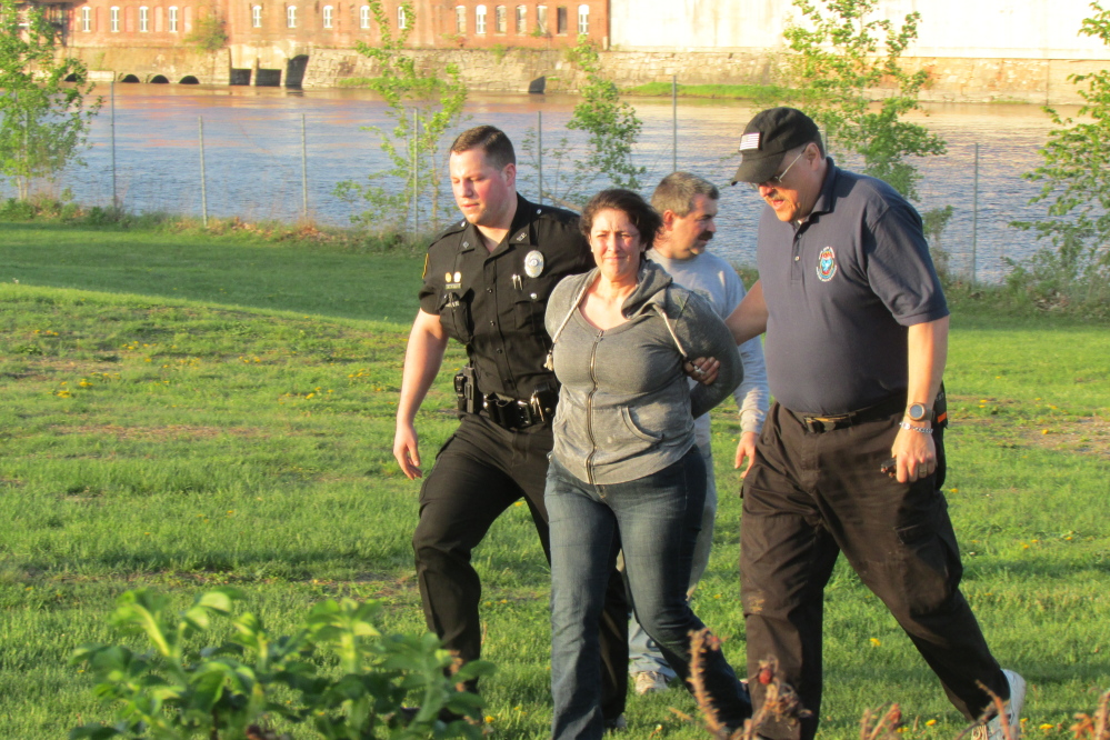 A woman is taken into custody by Winslow Police Officer Alex Jones and Waterville Fire Chief David LaFountain near the Two Cent Bridge in Waterville Tuesday evening.