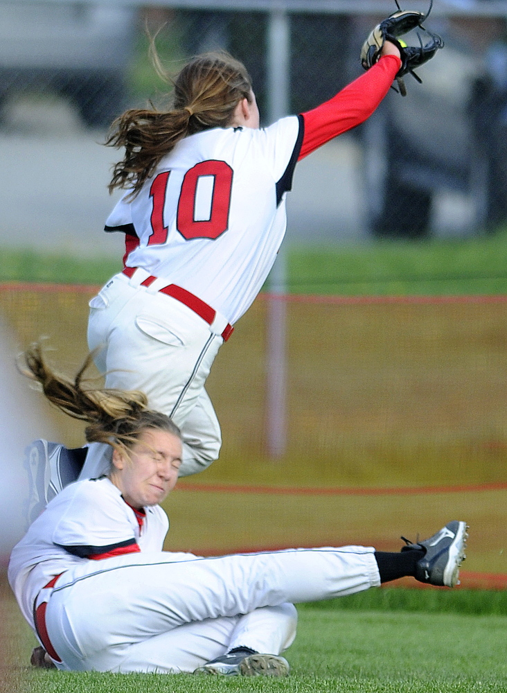 Hall-Dale High School's Olivia Maynard, bottom, collides with Mt. Abram's Nicole Bodge while pursing a popup in left field during a Mountain Valley Conference game against Hall-Dale on Wednesday in Farmingdale. Bodge was knocked to the ground but came up with the catch.