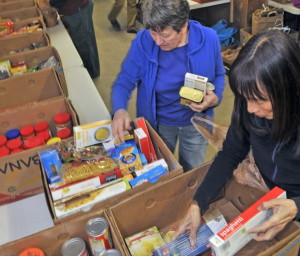 Eleanor Kidwell, left, and Alyssa Wingate sort donated food on earlier this month at the Augusta Food Bank.