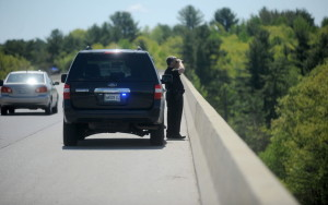 Winslow police officer Shawn O'Leary looks for a possible jumper off Carter Memorial Bridge on Friday.