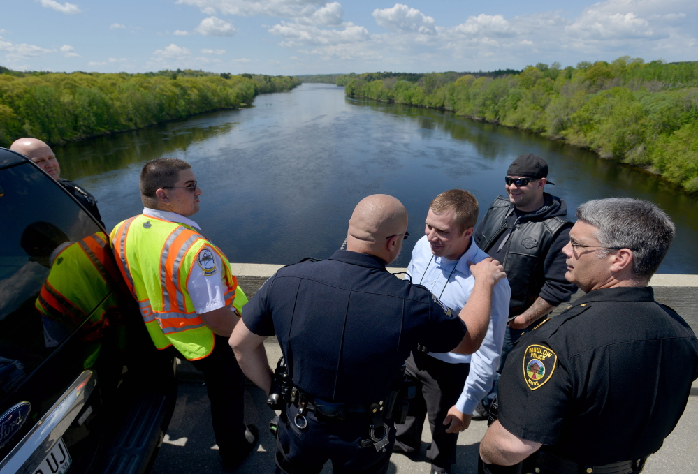 Police officers and firefighters from Waterville and Winslow stand on Carter Memorial Bridge after a report that a man seen on the bridge possibly jumped off it Friday morning. Emergency responders looked in the river, but found nothing.
