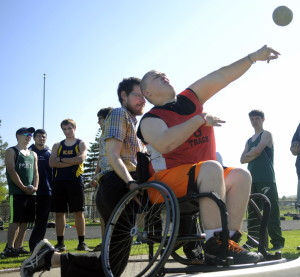Staff photo by Andy Molloy   Anchored by assistant coach Joe Fitzsimmons, Gardiner Area High School student RJ Sullivan competes in the shot put during a meet Thursday in Gardiner.