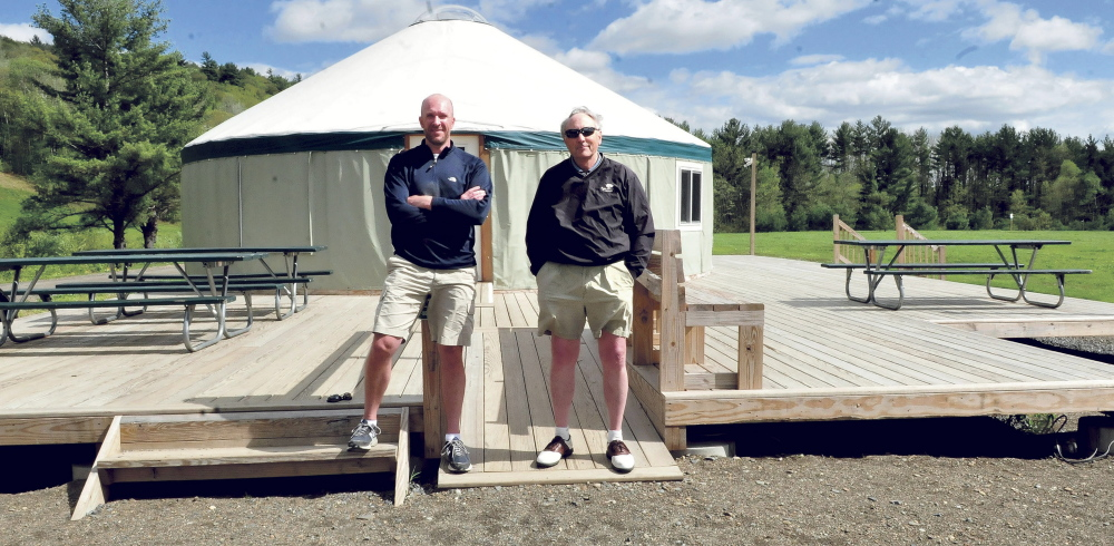 Matt Skehan, left, director of Waterville Parks and Recreation, and John Koons stand in front of a yurt on Wednesday at the Quarry Road Recreation Area in Waterville. Officials are trying to raise the final part of a Harold Alfond Foundation grant match to complete upgrades at the site.