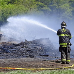 Firefighters extinguish remaining hot spots after a fire destroyed a long chicken barn Saturday in Pittston.
